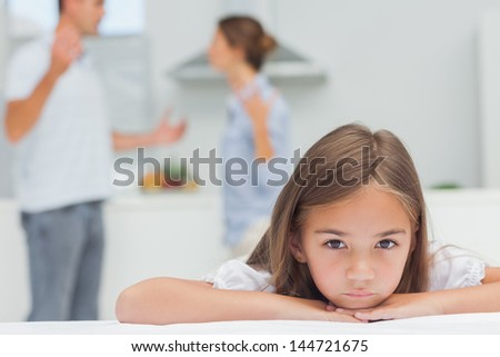 Upset girl listening to parents quarreling in the kitchen - stock photo