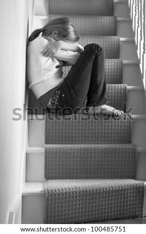 Upset girl on the stairs - stock photo
