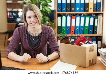 Upset girl with fists clenched in anger sitting behind a desk - stock photo