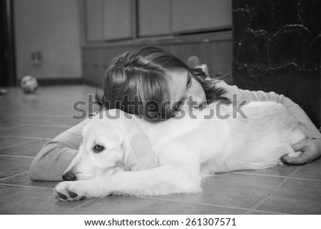 Upset girl with her friend, golden retriever. Monochrome photo - stock photo