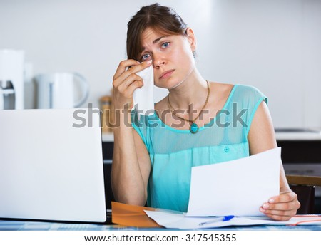 Upset housewife reading banking statement in the kitchen - stock photo