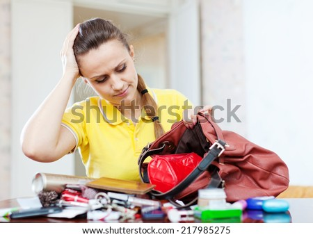 Upset inconsiderate woman lost something  in her purse - stock photo