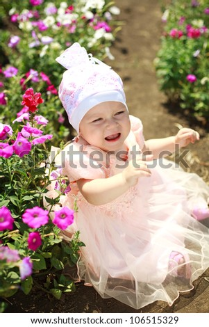 Upset little baby in flowers field