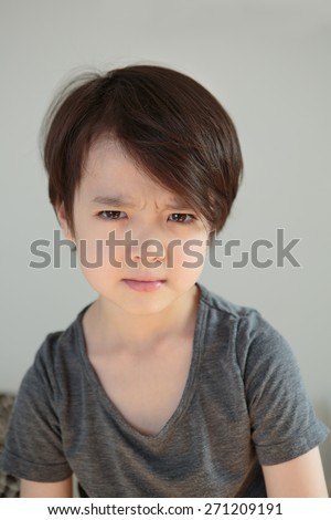Upset little boy, holding in his emotions. Tearful child. Dramatic kid. Angry young youth with tears in his eyes. Childhood depression concept. Children's mental health. Working through problems. - stock photo