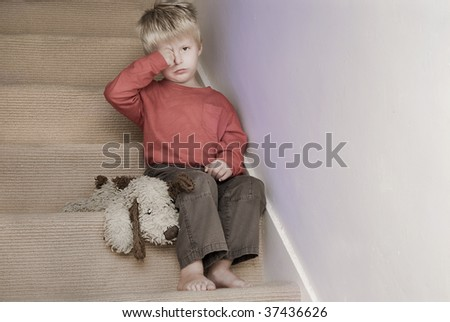 Upset little boy sitting on the stairs. - stock photo