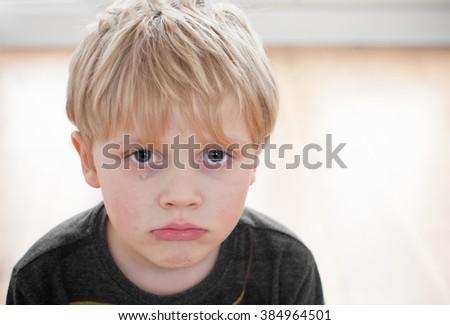 Upset little boy with tear on cheek - stock photo