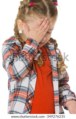 Upset little girl crying with hand covering the face. Closeup - Isolated on white background.The concept of a Happy childhood and child development - stock photo