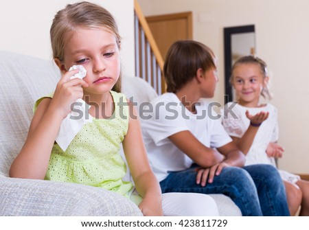Upset little girl is jealous sister of stepbrother and crying indoors