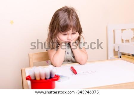 upset little girl sitting at the desk at school - stock photo