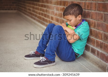 Upset lonely child sitting by himself on the elementary school grounds - stock photo