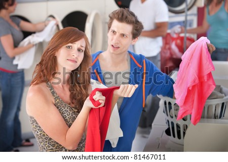Upset man and woman with stained clothes in laundromat - stock photo