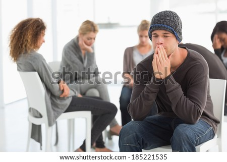Upset man at rehab group with hands to face at therapy session - stock photo
