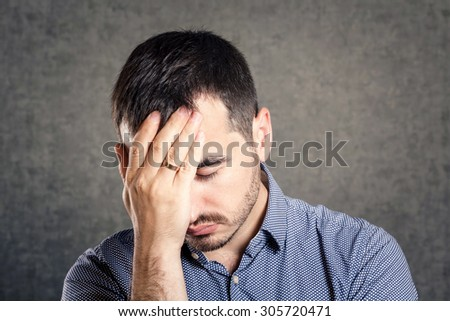 Upset man holding his head - stock photo