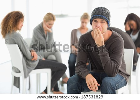 Upset man in rehab group looking at camera at therapy session - stock photo