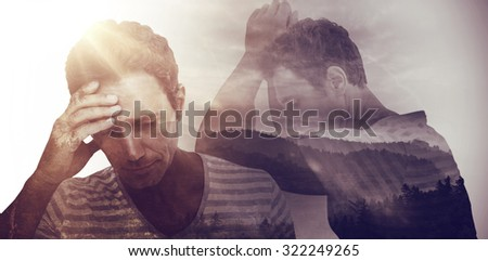 Upset man leaning on white background against trees and mountain range against cloudy sky - stock photo