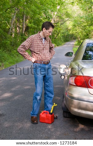 Upset man on a country road, staring at the empty gas tank of his car with a gas can at his feet. - stock photo