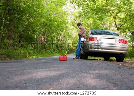 Upset man stranded on a country road, with a gas can at his feet. - stock photo