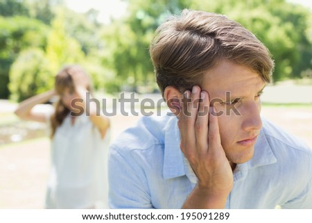 Upset man thinking after a fight with his girlfriend in the park on a sunny day - stock photo