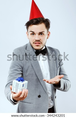 Upset man, wearing in white shirt and santa hat, posing with present in his hand, on white background, in studio, waist up - stock photo