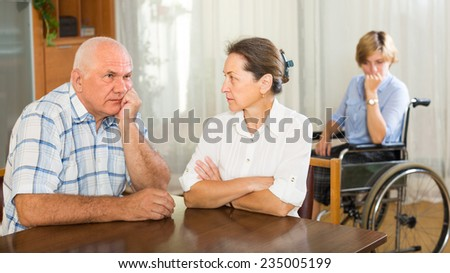 Upset mature couple and handicapped female having domestic quarrel. Focus on woman  - stock photo