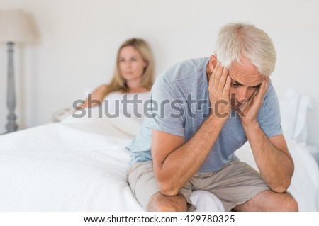 Upset mature couple ignoring each other. Close up of a worried senior man in tension at bed. Senior couple angry with each other after a fight.  - stock photo