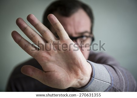 Upset mature man show stop sign with his palm - stock photo