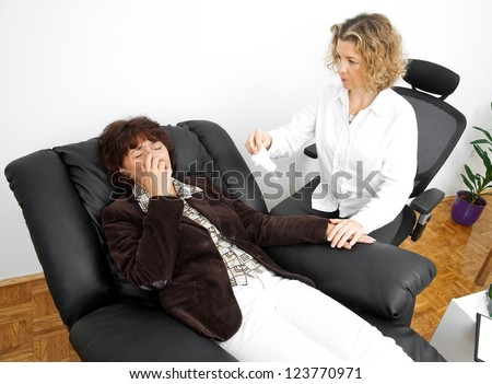 upset mature woman in therapy laying in psychiatrist office chair - stock photo