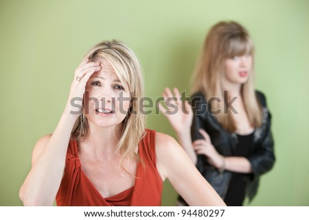 Upset mom with frustrated daughter over green background