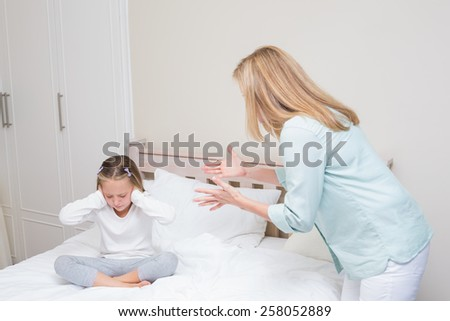 Upset mother scolding her daughter in the bedroom - stock photo
