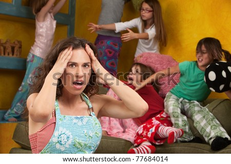 Upset mother with hands on head among mischievous little girls - stock photo