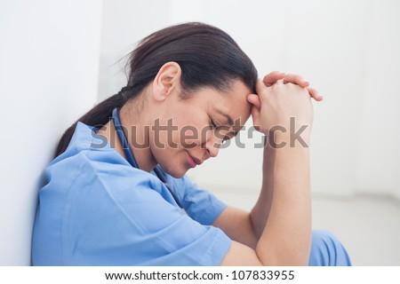 Upset nurse sitting on the floor in hospital ward - stock photo