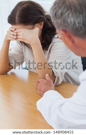 Upset patient crying while doctor comforting her in bright surgery - stock photo