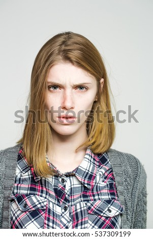 Upset pretty girl or cute beautiful woman female model with blonde hair in plaid shirt and knitted coat frowns on grey background