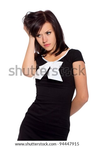 upset pretty woman sad looking down, young girl wear black dress with white bow, isolated over white background, concept of depression, stress and problems