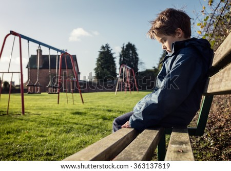 Upset problem child sitting on play park playground bench concept for bullying, depression, child protection or loneliness - stock photo