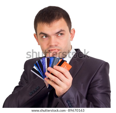 Upset Robed man Glaring At his Many Credit Cards. - stock photo