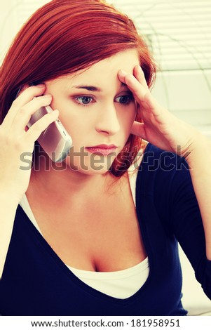 Upset, sad and worried by problems young woman sitting and talking by the phone.  - stock photo