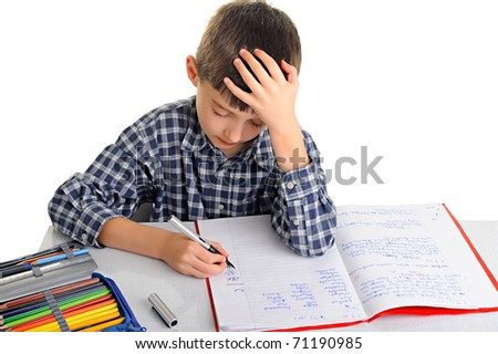 Upset schoolboy doing homework isolated on white - stock photo