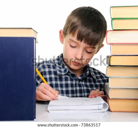 Upset schoolboy doing homework isolated on white - stock photo