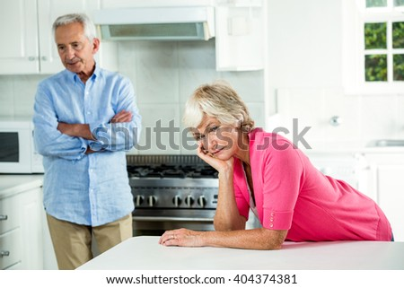 Upset senior couple after argument while standing in kitchen