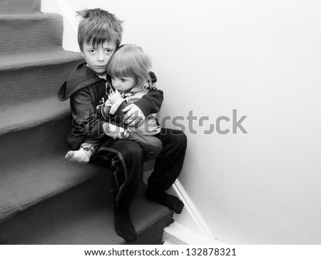 Upset siblings sitting on the stairs. - stock photo