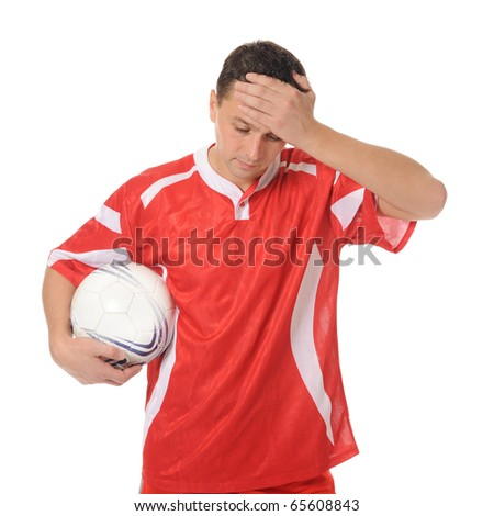Upset soccer player in the red form. - stock photo