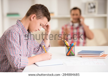Upset son sitting at the desk while his father talking on phone. - stock photo