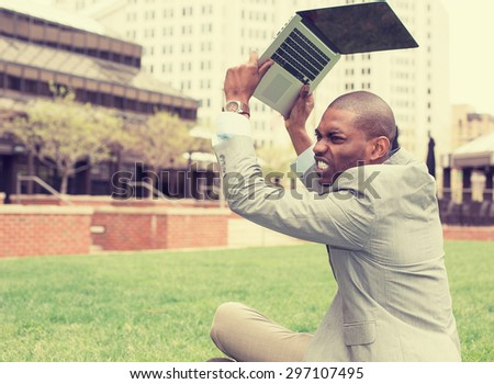 Upset stressed, angry business man throwing his tablet computer, laptop sitting outside corporate office. Negative human emotions, facial expressions, feelings, reaction, life perception - stock photo