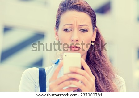 Upset stressed woman holding cellphone disgusted with message she received isolated corporate building background. Sad looking human face expression emotion feeling reaction perception body language - stock photo