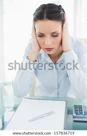 Upset stylish brunette businesswoman holding her head and looking away in bright office