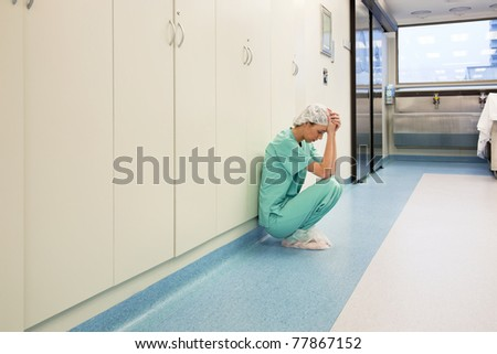 Upset surgeon sitting alone after she failed an operation - stock photo