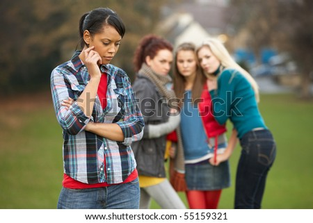 Upset Teenage Girl With Friends Gossiping In Background - stock photo