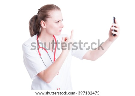 Upset woman doctor or medic showing middle finger over video call using smartphone - stock photo