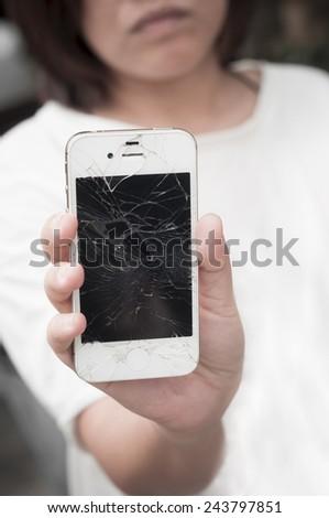 Upset woman holding broken mobile smartphone - stock photo